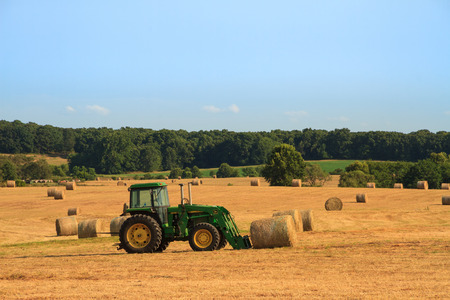Roscoe, Missouri7232017John Deere Tractor in a hayfield ready to lift a bale of hay.  Hay is used to feed to livestock.