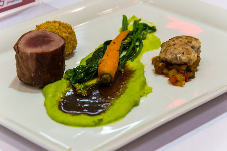 frence: grille pork tenderlion serve asparagus puree mince pork and baby carrot variety of taste and texture food stylish and frence cuisine