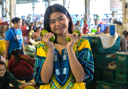 the girl smile with lime in morning market in thailand