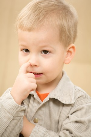 Boy with finger in the nose in a corduroy shirt