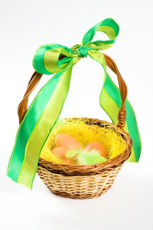 Easter wicker basket with eggs and ribbon photo