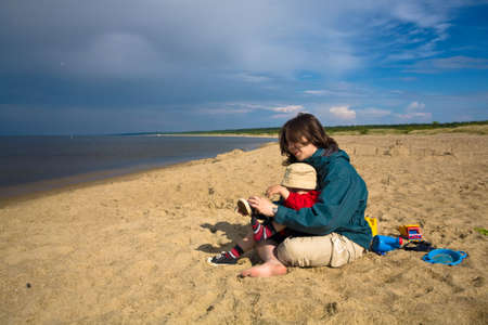 Mom with a son on the beach after the rain, on the Baltic Sea Stock Photo - 4783470