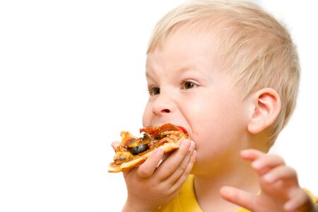 eat smeared: Little boy eating pizza with appetite.