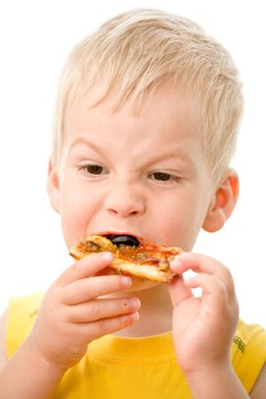 Little boy eating pizza with appetite. photo