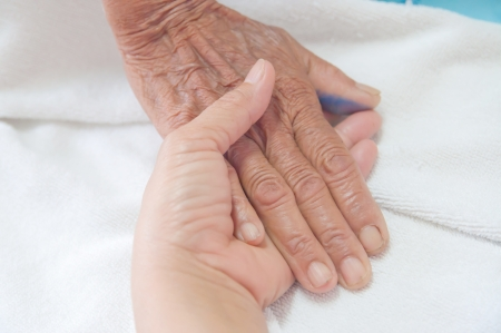 A young hand touches and holds an old wrinkled hand  photo