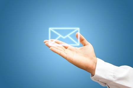Mão com símbolo do correio no fundo azul Imagens