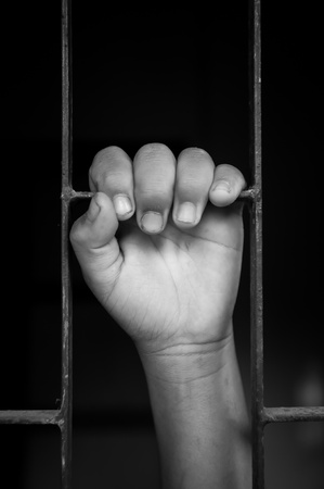 prisoner of war: hands of a girl are grabbing steel cage