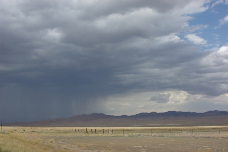 approaching: Rainstorm over the mountains is coming to the field. Stock Photo