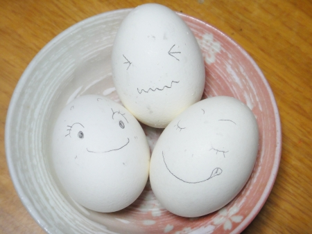 three eggs drawn faces with a pencil