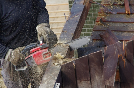 The beam of the house is being cut by a chainsaw