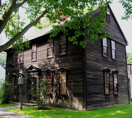 earlier: Colonial home in the shade of a tree. Stock Photo