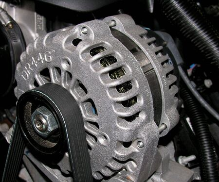 alternator: An Alternator used to power the electrical system on an automobile. Stock Photo