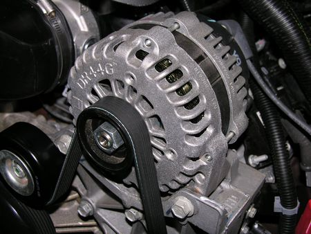 Alternator and drive belt on an automobile.