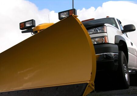 Snowplow and truck against clouds. 스톡 콘텐츠