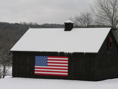 white winter: American flag on barn in snow.