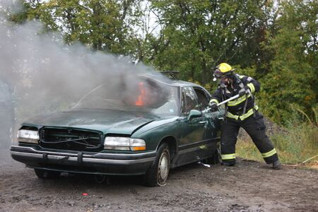 Firefighter on the scene of a car fire 스톡 콘텐츠