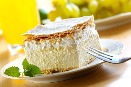 custard: Piece of cream and custard pastry with melissa and grapes Stock Photo