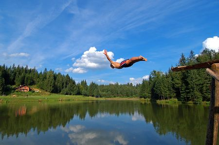 Young boy jumping in alpine lake in Slovenia Stock Photo