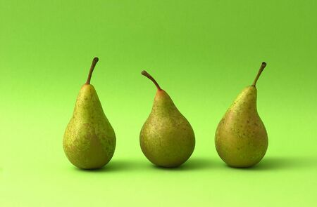 Three pears on green background                               Stock Photo