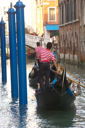 Gondoliers in small canal in Venice