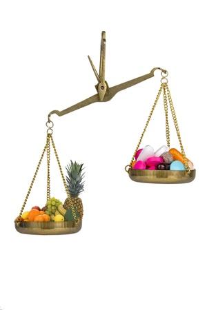 antibiotic: Pills versus fruit weighted on yoke,nature against chemistry on white background. Stock Photo