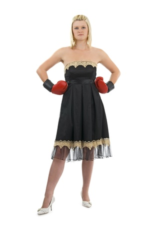 Woman in black dress and boxing glove on egg white background.Possible financial context.On white background.