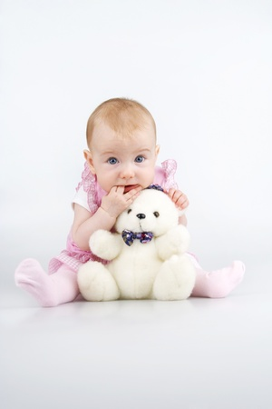 white blanket: Child with plushy cuddle-bear and by two fingers in mouth,on white background.