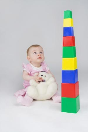 plushy: Wonderstruck little girl with plushy cuddle-bear and playing devils-bones,on white background. Stock Photo