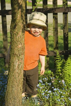 A little boy palms  behind the tree. Stock Photo - 12208156