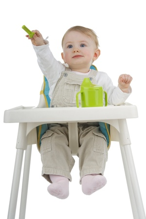 highchair: Child on childs stool with potty and teaspoon on white background. Stock Photo