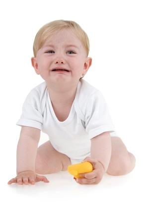 Weinend Kleinkind mit Spielzeug auf weißem Hintergrund.