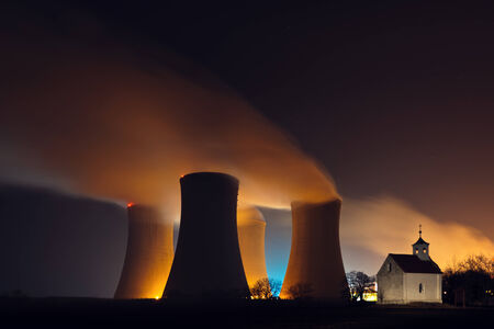 Nuclear power plant cooling towers with steam behind a small chapel photo