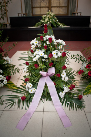 crematorium: Large funeral flowers in wreath with ribbon on floor Stock Photo