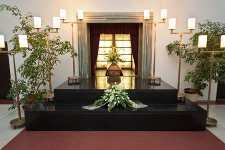 crematorium: Wooden coffin with funeral flowers in crematorium Editorial