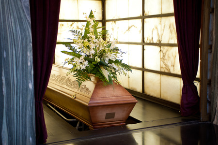 coffin: Wooden coffin with funeral flowers in crematorium Editorial