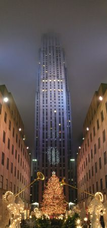 Angel playing trumpet for christmas and high tower in the back with blue fog - New York - Panorama. Stock Photo