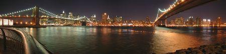 Dos puentes de Brooklyn, uno por la noche - Nueva York - Panorama.  Foto de archivo