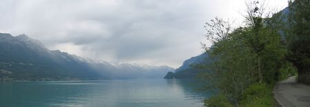 Lake Interlaken and a shore road with the Alps mountains in the backgound - Switzerland - Panorama. photo