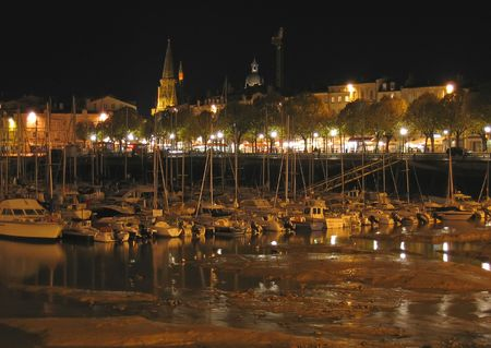 steely: Harbour by night with the city - La Rochelle - France. Stock Photo