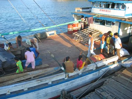 Indonesian people boarding on a local boat - Togians island - Sulawesi - Indonesia. photo