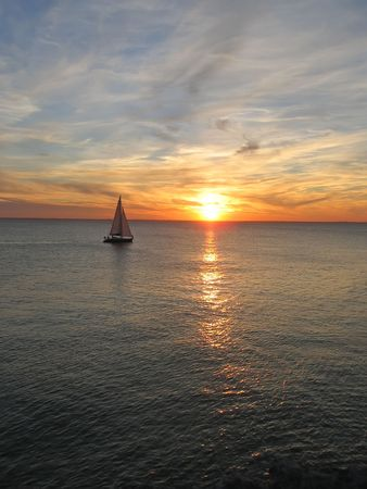 Sunset over the sea with a sailing boat cruising - France. photo