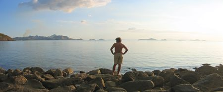 A man looking over the infinite tropical sea and island archipelago - Labuan Bajo - Pede Beach - Flores island - Indonesia. photo