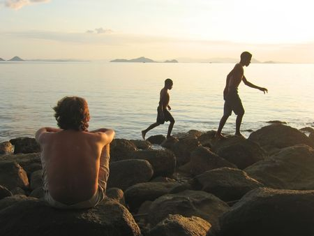 A man looking over the infinite tropical sea with two indonesian boys walking in front of him - Labuan Bajo - Pede Beach - Flores island - Indonesia. photo