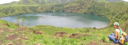 steely: Blue lake with a trekker woman sitting near - Cameroon - Africa - Panorama.