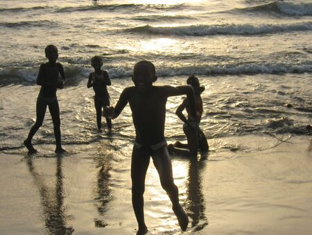 Young african childrens playing at the sunset on a tropical beach - Cameroon - Africa.