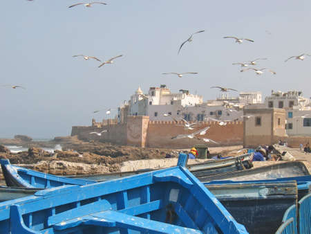 rampart: Sea gull over the harbour and the city rampart with a blue boat on the foreground - Essaouira - Morocco. Stock Photo