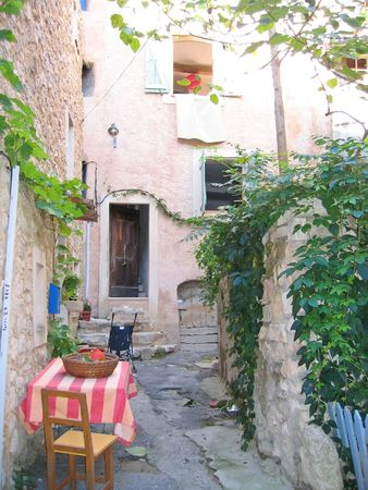 azur: Small provencal city path with chairs and a coloured table - Azur coast - South of France. Stock Photo
