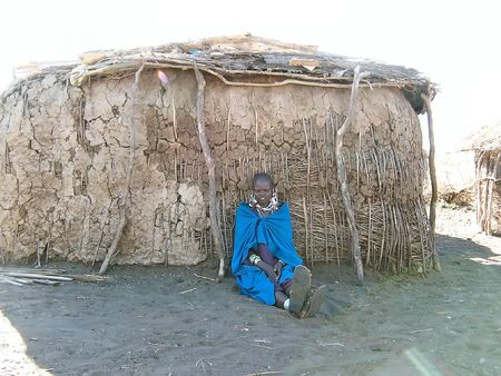 sitted: Massai girl sitted in front of her hut - Serengeti park - Tanzania. Stock Photo