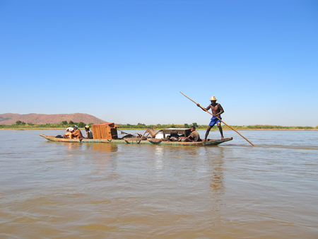 steely: Man standing on a dugout canoe - The Tsiribihina river - Madagascar.