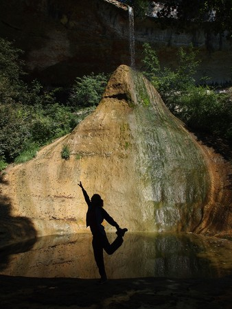 A girl making meditation exercice in natural place with a river falling on a big white and yellow rock - The Pain de Sucre - France - The Alps. Stock Photo
